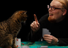 Poker cat. Young smiling red-haired bearded man in glasses holds finger up playing poker with tabby cat sitting at gaming table on black background Stock Photo
