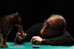 Poker with cat. Young smiling red-haired bearded man in glasses playing poker with tabby cat sitting at gaming table on black background Royalty Free Stock Image