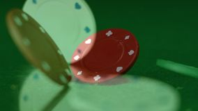 Poker chip thrown on table. Digital composite on red poker chip thrown on the green poker table while poker chips falling on the table on the foreground in stock footage