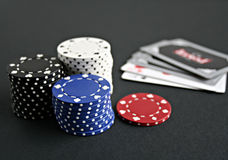 Poker Chips. Stacks of multi-colored poker chips with cards in the background royalty free stock photo