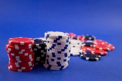 Poker Chips. Stacked on a blue background stock image