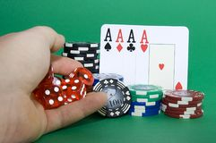 Poker Chips. Hand rolling dice sith poker chips and cards Stock Image