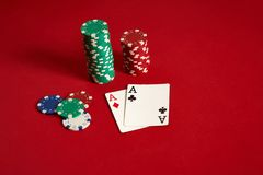 Poker chips and aces on red background. Group of different poker chips. Casino background. Royalty Free Stock Photography