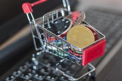 Poker chips and a bitcoin in a trolley on a computer keyboard. Online Gambling concept.  royalty free stock photos
