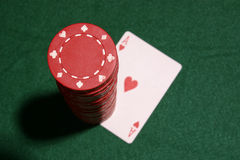 Poker chips on card. Red poker chips stacked on the ace of hearts Stock Photography