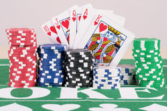 Poker Chips With Cards. Poker chips in five different colors on a table with cards Royalty Free Stock Photography