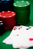 Poker chips and cards. A few poker chips and a good hand on a green underground Stock Photography
