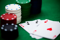 Poker chips and cards. A few poker chips and a good hand on a green underground Stock Image