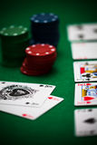Poker chips and cards. A few poker chips and a good hand on a green underground Stock Images