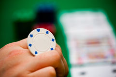 Poker chips and cards. A person playing with a poker chip, in the background you can see some cards and some poker chips Stock Photography
