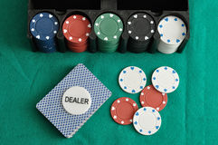 Poker chips and cards. A deck of card with the dealer chip and some poker chips Royalty Free Stock Image