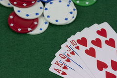 Poker chips and cards on a green table. Close up of poker chips and cards on a green table royalty free stock image