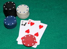 Poker chips and cards. Two poker cards (seven and six) on a poker tabel and stack of chips stock photography
