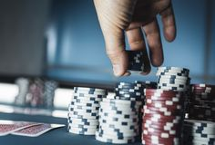 Poker chips at casino. Lucky player stacking poker chips at casino, gambling and bet concept stock photo