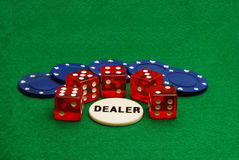 Poker Chips and Dice. A gambler's arsenal of poker chips and dice with a dealer chip nearby Stock Photos
