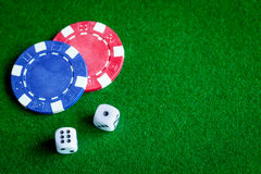 Poker chips and dice on green background top view Royalty Free Stock Photos