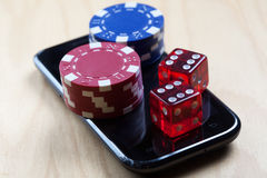Poker Chips and Dices on top of cell phone. Concept shot with poker chips on a mobile phone and dices - online gambling, mobile gaming etc Stock Photos