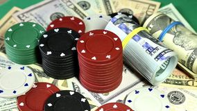 Poker chips and dollars on rotating surface.