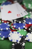 Poker Chips and Four Aces. Four Aces and poker chips on a green felt casino table with the focus on the chips stock images