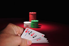 Poker chips. Four of a kind. A man looks at his hand: four aces and a king. In the background are several stacks of casino chips of various heights and colors royalty free stock images