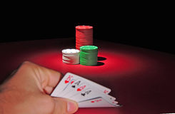 Poker chips. Four of a kind. A man looks at his hand: four aces and a king. In the background are several stacks of casino chips of various heights and colors Stock Photo
