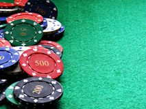 Poker chips on green felt table. A selection of various value poker chips on a green felt poker table background with copy space royalty free stock photo
