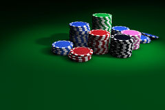 Poker Chips On Green Table. Gambling casino chips stacked on green table. Great background for poker magazines, banners, webpages, flyers, etc Stock Image