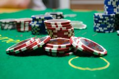 Poker chips with playing cards on a green table. Poker chips grouped on the table. In front red chips and back some blue chips Stock Images
