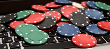 Poker chips on laptop stock image