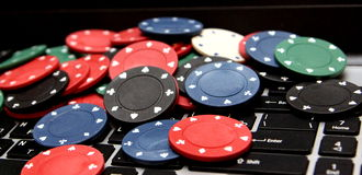 Poker chips on laptop Stock Photography