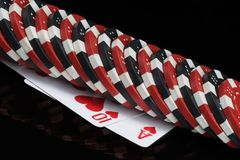 Poker chips lie in a row on two playing cards, black background stock image