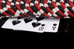 Poker chips lying on playing cards, concept on black background royalty free stock photography