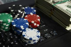 Poker chips and packs of dollars on a laptop royalty free stock photography