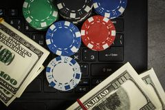 Poker chips and packs of dollars on a laptop stock images