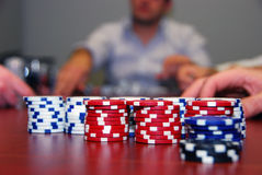Poker Chips with Players in Background. Piles of poker chips get handed out to players at a friendly home poker game Stock Photo