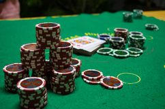 Poker chips with playing cards in a green table. Some poker chips with playing cards in a green table in a close photography. The red chips are in the front and Royalty Free Stock Photography