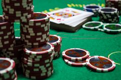 Poker chips with playing cards in a green table. Some poker chips with playing cards in a green table in a close photography. The red chips are in the front and stock photo