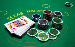 Poker chips with playing cards in a green table. Some poker chips with playing cards in a green table in a close photography. The red chips are in the front and royalty free stock images