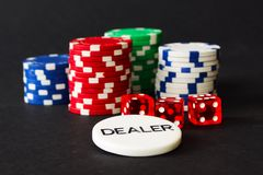 Poker Chips with Red Dice in forground on black backgrund with reflections. Poker Chips and Red Dice play with dealer badge in foreground and black background in royalty free stock image