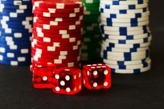 Poker Chips with Red Dice in forground on black backgrund with reflections. Poker Chips and Red Dice play with black background in close up stock images