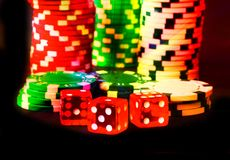 Poker Chips with Red Dice in forground close up on black backgrund, color fantasy, Vegas style. Poker Chips with Red Dice in forground close up on black stock photo