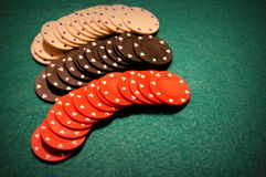 Poker chips in a row. Three lines with poker chips on a green table stock photo