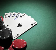 Poker chips with royal flush. Several stacks of casino chips of various heights and colors with a royal flush, all sitting on a green colored playing surface Stock Image