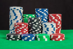 Poker chips stack on green table black background Royalty Free Stock Photography