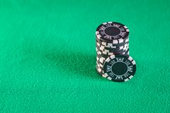 Poker chips stacked on green table Stock Photo