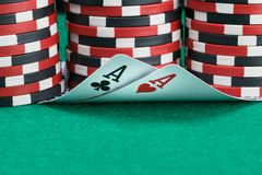 Poker chips stand as background for two playing cards lying on a green table royalty free stock photos