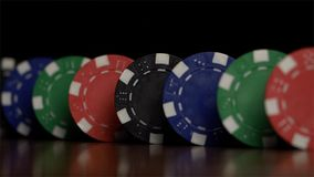 Poker chips stand in a row on a black background, a Domino effect. Playing poker chips are on the table, a symbol of royalty free stock images