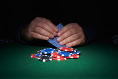 Poker chips on table with hands and cards Royalty Free Stock Image