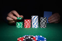 Poker chips on table with hands and cards Stock Photos