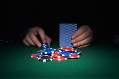 Poker chips on table with hands and cards Stock Images